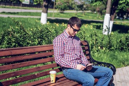 シャツとジーンズのサングラス、タブレット上で見る男はベンチ、実業家休暇の概念に夏のソーシャル ネットワークに対応します。都市生活。 公園