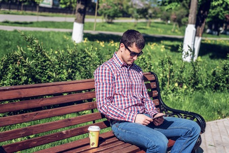 man in  shirt and jeans  sunglasses, video looks on the tablet corresponds to the social networks, in the summer  the bench, the concept of  businessman  vacation. City lifestyle.  the street in the park. Happy emotional. Next cup  coffee or tea. Stock Photo