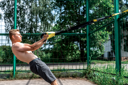 Man is an athlete, trains in nature in the city, summer trx training, Balance motivation, tanned skin in shorts. Exercise in the arms. Stock Photo