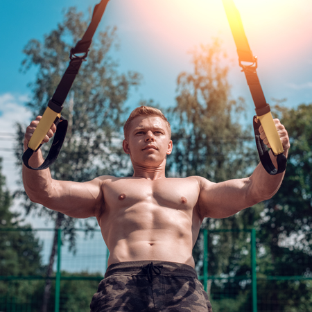A male athlete is engaged in the open air loops, trains the biceps. In summer, in shorts and a bare torso. Healthy lifestyle of young people. The concept of sport motivation. Close-up.