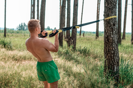 Male athlete excellent training training loops, fresh air nature in summer forest, feel your strength, motivation. Exercise of the biceps muscles. A sunny day. Stamina man. A Stock Photo