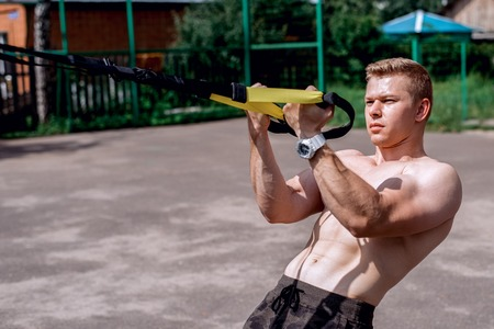 A male athlete is engaged in an open air loop, coaches a bicep fence. In summer, in shorts and a bare torso. Healthy lifestyle of young people. The concept of sport motivation.