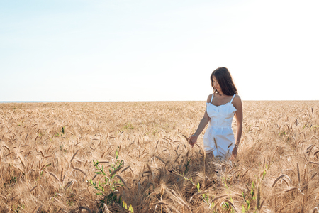 Beautiful summer girl in a wheat field, in a white dress, tanned skin, happy on vacation in the fresh air. A sunny day. Teenage model. happiness, nature, summer holidays, vacation and people concept