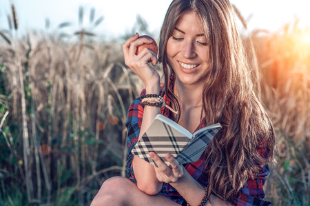 Beautiful girl student in the field. In his hand is an apple. Concept of new ideas, smiling, in summer on nature. In his hand a notebook, long hair. Clever ideas. Inspiration by creativity. Reads the diary.