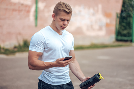 he: A man reads a message on the phone, holds in his hand a bottle of water, an energetic protein. Responds to the call in social networks. He rest after training. In the city in the fresh air.
