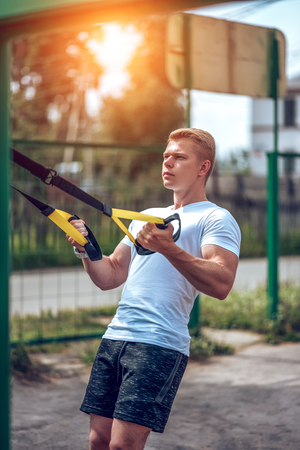 Male athlete, engaged in hinges, doing physical exercises. Exercise in the fresh air. The concept of a healthy lifestyle. The athlete is engaged on the loops swings the chest back. Stock Photo