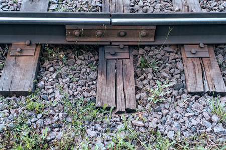 Gravel with grass. Old sleepers, in the city there is a tram line. In nature, a wet wooden board. Coupling of metal rails.