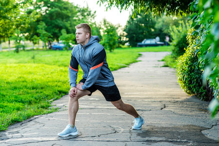 A male athlete warms up before jogging in park. Listens to music on headphones.