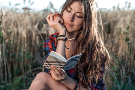 Beautiful girl student field. In his hand apple. Concept new ideas, outdoors, summer in nature. In his hand a notebook, long hair. Clever ideas. Inspiration by creativity.
