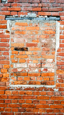 The brick wall, the window is bricked, the old cement red brick in the summer in city, a building that is abandoned.