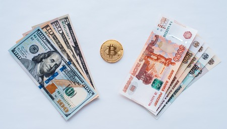 On a white background, the exchange of Russian rubles on US dollars on a metal coin bitcoin in paper money from crypto currency.