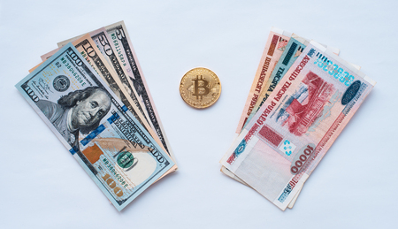 On a white background, exchange currency Belarusian rubles on dollars usa on a metal coin bitcoin in paper money from crypto currency.