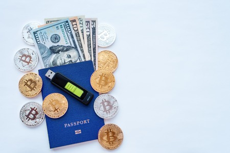 Blue passport, white background, identity confirmation. Memory card USB stick purse. Security code cold wallet. US dollars USD metal coins gold silver bitcoin, crypto currency customer identification. Stock Photo