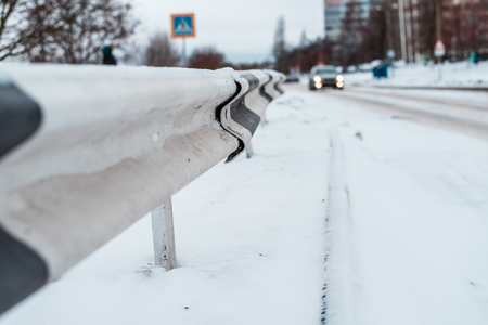 Close-up of the bump in winter on the road, in winter in the city the car is far away.