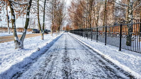 The cleared road in the park, cleaned in the winter in the city, the road cleaned by a sunny day. Asphalt in the snow next to the fence.