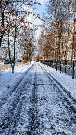 The cleared road in the park, cleaned in the winter in the city, the road cleaned by a sunny day. Asphalt in the snow next to the fence. Stock fotó - 95398116
