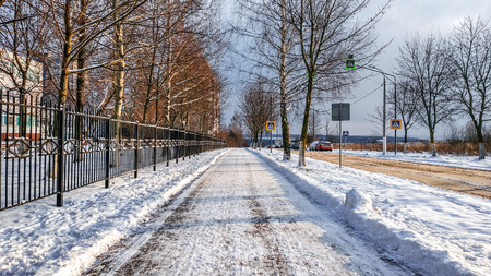 Road in the city in the winter, cleaned snow cleaned the street from the snow in the park. Reklamní fotografie