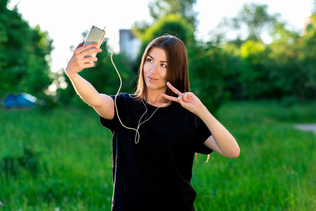 Happy Asian girl smiling at the camera. To call by video call. Speaks on the phone listening to music. Hand gestures. Hello. Summer in the field on a green meadow. He speaks in social networks.
