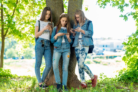 Three teenage girls stand by tree in summer park. In his hands holds smartphone and communicates social networks. Corresponds with parents concept of internet addiction. Friendly communication. 写真素材