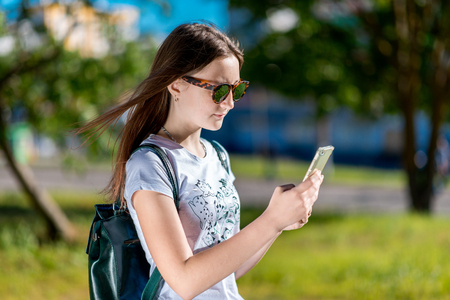 The brunette girl in sunglasses. In the summer in the open air. Behind the backpack. In his hands holds a smartphone. Corresponds with friends. The teenager after school is on break. 写真素材