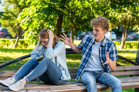 Summer in nature. The guy yells girl gesturing with his hands. The girl covered her head with hands covering ears. The concept of aggression in a relationship. Scandal in family.