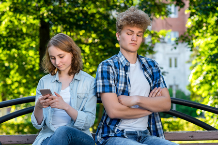 Young beautiful couple. In summer park nature. They sit on a bench. The girl corresponds in social networks. The guy is watching sms. Concepts mistrust in relationships. Peeping one after another.