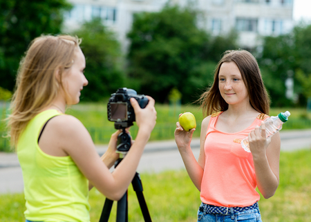 2 girls are teenagers. In the summer in park in nature. Writes the video to the camera. Heres how to hold an apple and a bottle of water. The concept of young bloggers. Use camera with tripod.