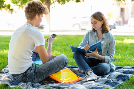 A guy with a girl in the summer in nature. They are sitting in the fresh air. Do lessons after school institute. Hands holding a smartphone a large summary. Performs his homework.