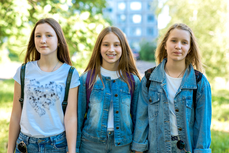 Three girl friends girl schoolgirl. Summer in nature. In jeans clothes behind backpacks. The concept is best friends, girlfriends, go to school. Emotion smiles happily.
