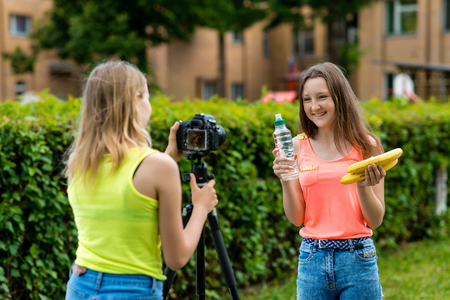 Girls girlfriends in summer in the park records video on the camera in a healthy diet. Hands holding a banana bottle of water happily and happily smiling.