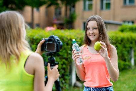 Girl girlfriend in the hands holding a bottle of water and a green apple. In summer he writes video to the camera in nature. The concept of the best friends of young bloggers. Stockfoto