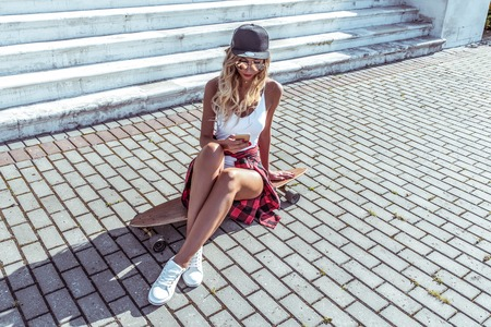 Beautiful tanned girl sitting on a skateboard. In the hands of holding a smartphone. Corresponds in social networks, communication in the Internet. Summer bright sunny day in city.
