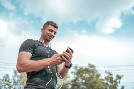 The athlete is holding a smartphone. Happy smiling, listening to music communicates on social networks. A man athlete calls ringing in headphones.