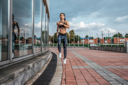 Girl athlete runs in a jump. In the city on a summer day. In his hand, the player listens to music on headphones. Tattoos on tanned skin. Sports and healthy lifestyle. Free space for text. Zdjęcie Seryjne
