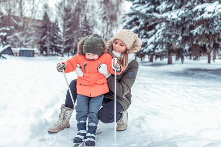 A little boy of 3-5 years old, gets up on skis for the first time, in the winter in a snowy forest. A young mother holds a child in the back. Active skiing, nature on a winter day. Happy smiles. Stock fotó