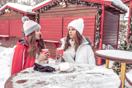 Two girlfriends in the winter in the fresh air in warm jackets and hats. They rest near the cafe, hold cups with hot coffee or tea in their hands. Communicate talking and warming up after a walk.