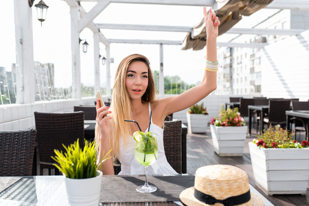 Beautiful girl in summer in a city cafe. With a gesture of hand, the waiter s covenant asks for a bill for breakfast or lunch. Business lady will make friends. Breakfast or snack at restaurant. Stock fotó