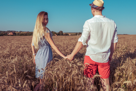 A girl with long hair in blue dress holding guy in shirt and red shorts by hand. Turns around looking at ass. They walk around wheat field in village. Romantic walk newlyweds, happy new family.