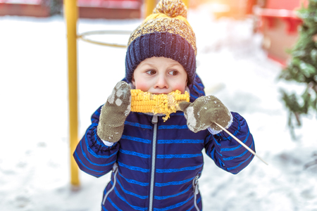 A little baby boy is eating boiled corn. In the winter afternoon on a walk. In a warm hat with a blue jacket and green mittens. The concept of healthy eating children.