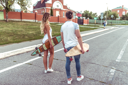 A young couple man and woman, in summer in city go on road, in hands of the board for skateboarding and longboard. In casual clothes and sunny view from the rear. Traveling in a new summer city.