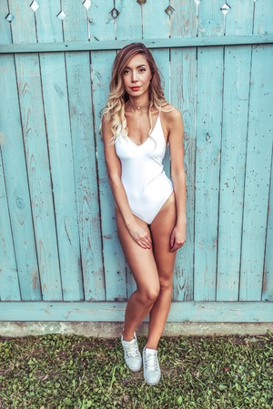 Beautiful girl in full growth, stands in the summer near the wooden fence. Woman In a white bathing suit body, with long hair and tanned skin. Outdoor recreation. Foto de archivo