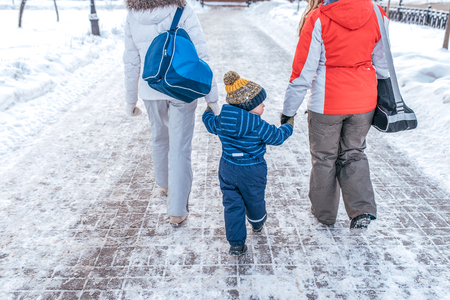 Mom and girlfriend sees boy s son 3-5 years old by the hand walking down the street. Back view. Winter in city on background of snowdrifts. Returning home from event. Two women girlfriends, parents.