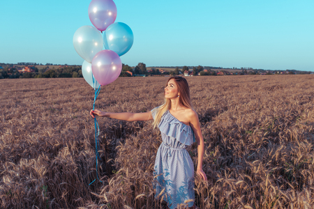 A girl in a summer wheat field holds balloons in her hand. After the party and holiday. Free space for text. The concept of fun airiness and holiday. Releases balls into the sky.