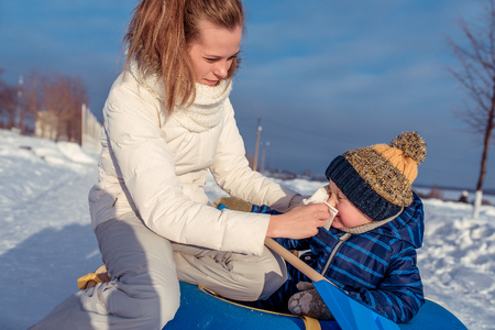 A young mother wipes snot and drool to her boy child. Prevention of the flu care for the child outdoors in the winter in open air, illness and cold.