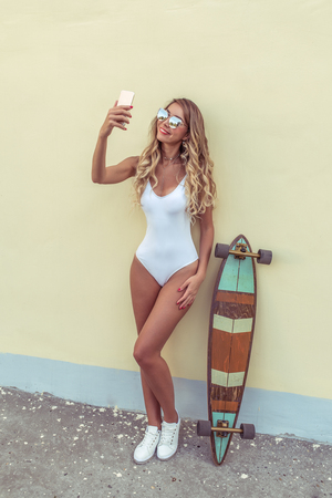Blonde girl beautiful bathing suit body, with longboard board. Summer day city. Hand, smartphone, photographs self in social network, online app Internet. Tanned skin long hair. Woman happy smiling. Stock Photo