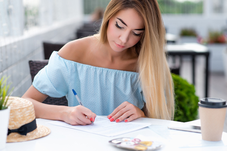 Beautiful girl summer cafe. Fills contract writing legal contract for services. Drawing up paper legally correct certified document. Woman long hair dress. Business lady working veranda restaurant.