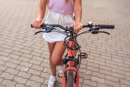Close-up of a red bike, the girl keeps parked behind the frame. In the summer in the city, the girl parks the bike, the black wheel, the clutch bell, close-up. Stockfoto
