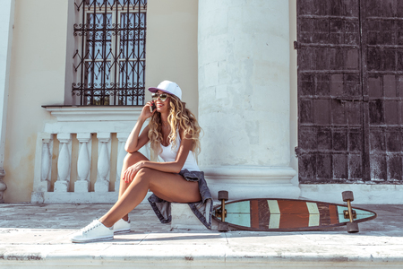 Beautiful girl in summer with board longboard skate phoning happy smiling. Online application video call to social networks. Emotions of joy and fun. Free space for text. Banco de Imagens - 118001441