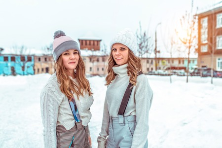 Two girlfriends girls students, in the winter in the city, a public rink. In casual clothes and warm hats. Happy smiling relax in nature in winter.