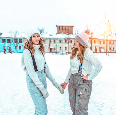 Two girlfriends girls students, in the winter in the city, a public rink. In casual clothes and warm hats. Happy smiling relax in nature in winter. Talk and lead the conversation. In warm overalls.